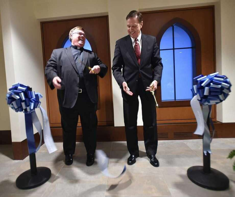 The Rev. Jordan Lenaghan, executive director of university religious life, and university President John L. Lahey cut the ceremonial ribbon to celebrate the opening of the Catholic chapel and Center for Religion Tuesday at Quinnipiac University in Hamden.