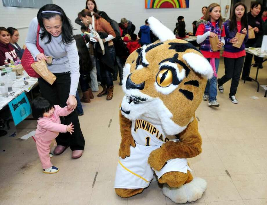 Photo by Arnold Gold/Register Meredith Huang, 1, (bottom left), of Hamden reaches out to Boomer the Bobcat (Chris Malico) during the SoHa Kids Fest at the M.L. Keefe Community Center in Hamden. At top left is her mother, Yamin Su.
