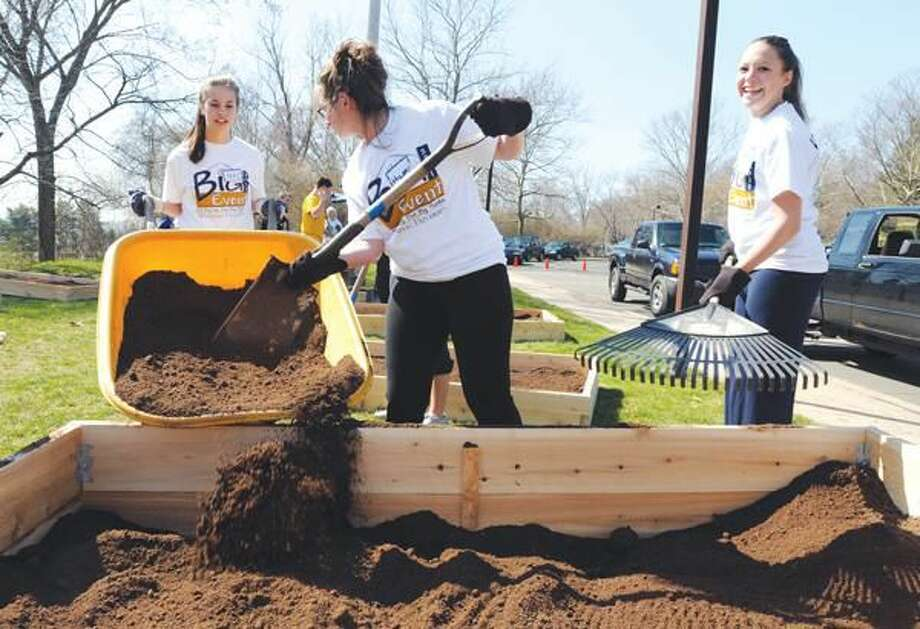 "Photo by Mara Lavitt Quinnipiac University students including, left to right, seniors Kelly Goldej, Hilary Good and Alyssa Mills, participated in a communitywide volunteer event called The Big Event by helping out at the Ridge Hill School's ""Dig In"" to build vegetable gardens."