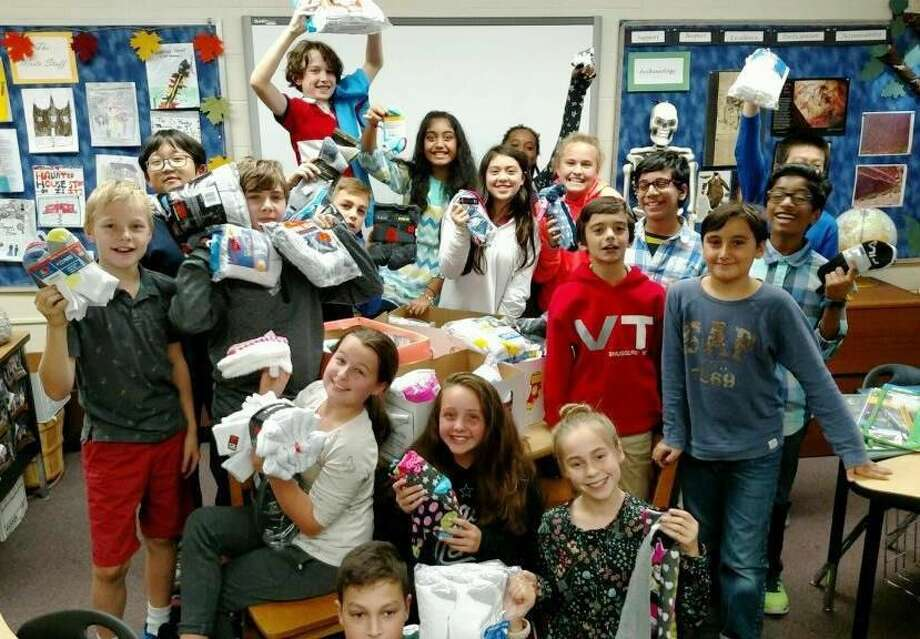 Sixth grade students with the socks they collected.
