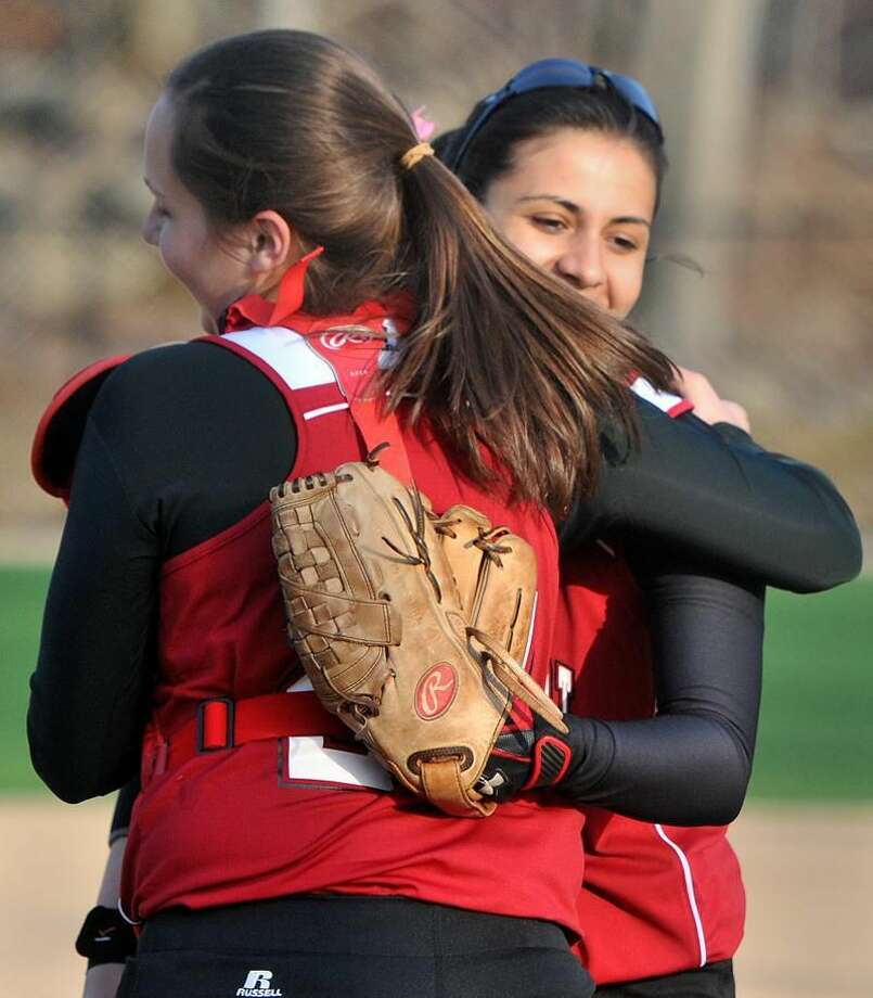 Photo by Brad Horrigan/Register Winning pitcher Molly Flowers, right, is congratulated by her Sacred Heart Academy teammate Angelika Stamos after their victory over Hand Friday afternoon.
