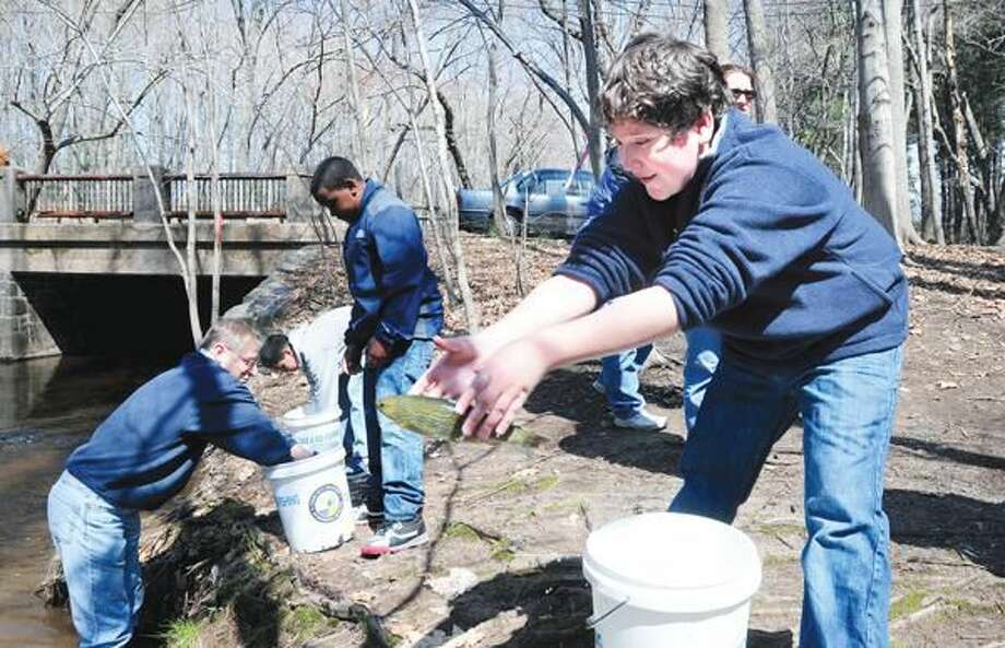 Photo by Arnold Gold Helen St. School fifth-grader Moises Zepeda (right), 10, and classmates stock trout into the Mill River in Hamden Friday.