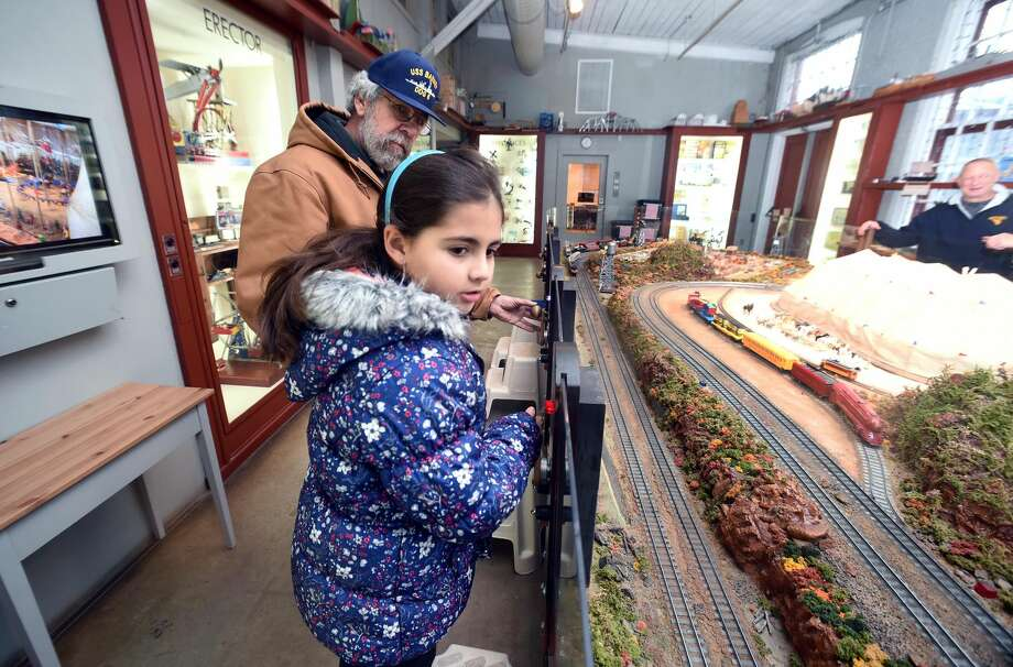 Bob Smith of West Haven and his granddaughter, Nyla Jaser, 8, of Milford activate trains at the Eli Whitney Museum's Mr. Gilbert Railroad American Flyer Trains exhibit in Hamden.