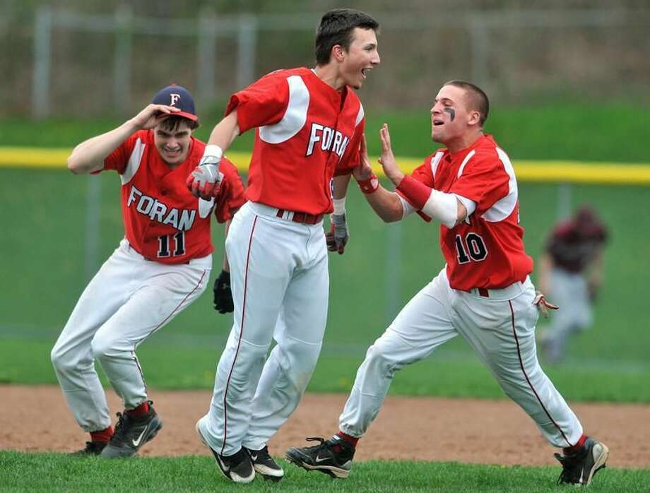 Photo by Brad Horrigan/Register Shawn Caraglio, Mike Deptulski and Tucker Schumitz celebrate Deptulski's game-winning RBI that beat North Haven Friday afternoon and sends Foran to the state tournament.
