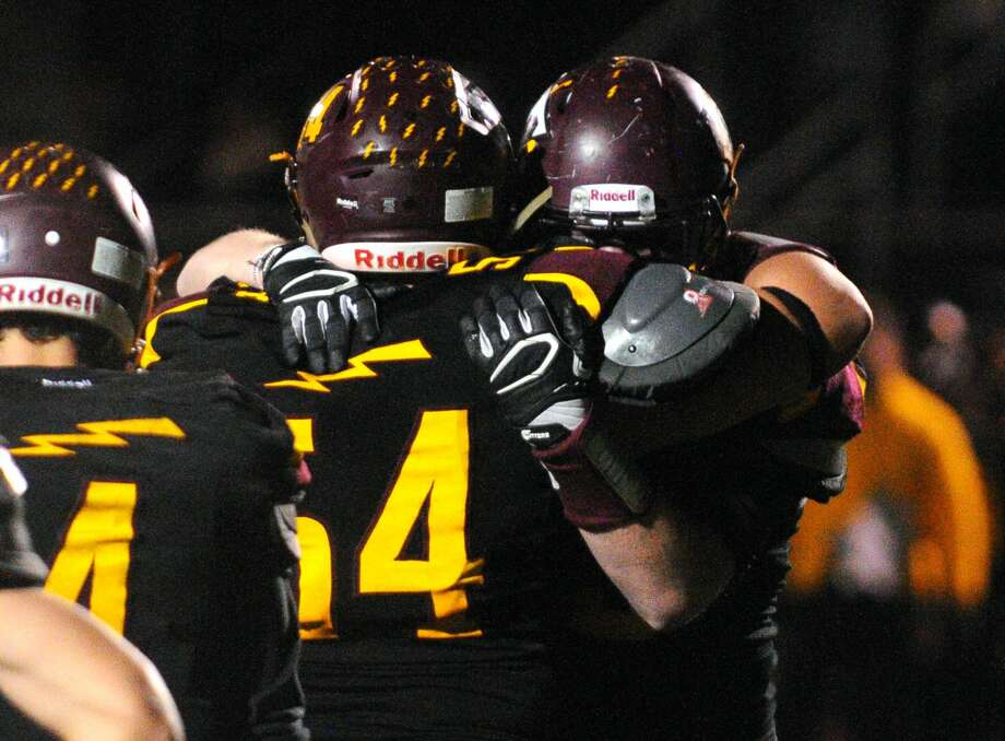 Sheehan's Stephen Zenisky (54) and a teammate embrace after the team was defeated by Joel Barlow during Class M football action in Wallingford, Conn. on Tuesday Nov. 28, 2017. Barlow advances to the semifinals.