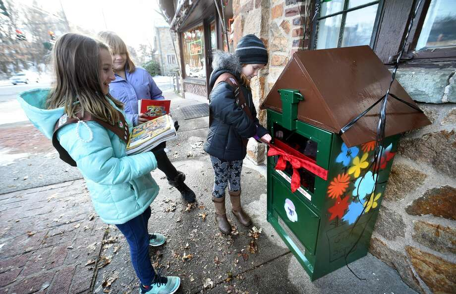 Left to right, Girl Scouts Troop 60651 Brownies Charlotte Trama, 8, and Aubrey Powers, 9, watch Ellie Solomon, 8, cut a ribbon on a New Haven Register vending machine transformed into a LIttle Free Library at 1630 Whitney Ave. in Hamden on Saturday.