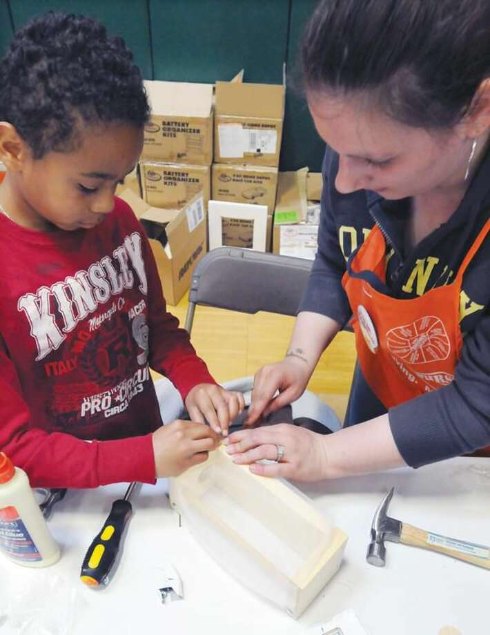 Photo by Mara Lavitt Hamden's Annual Business and Community Expo held at Hamden High School Saturday. Justin Brown, age 9, of Hamden, left gets help with his Bug House from Home Depot employee Teresa Zito, of New Haven, at the Home Depot booth.