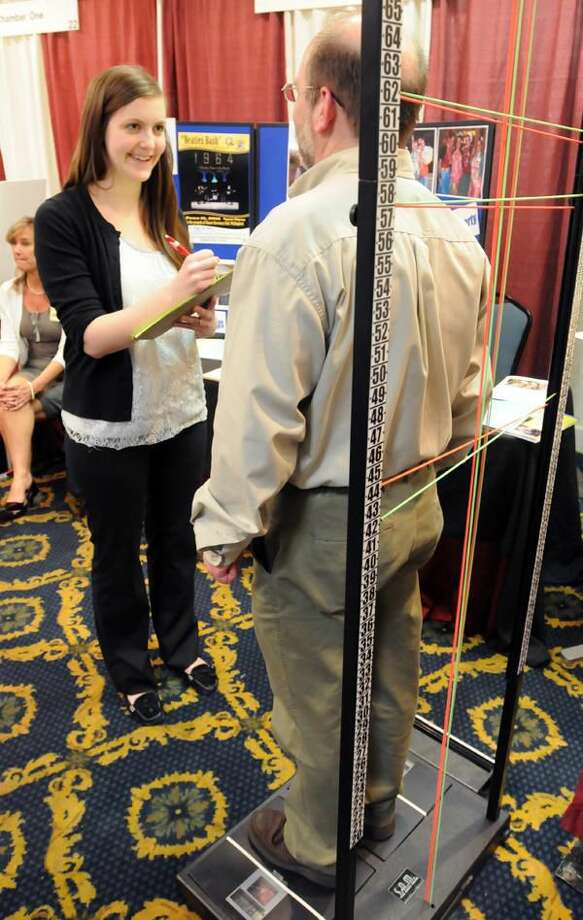 Photo by Mara Lavitt Ashley Dudgeon, of Wallingford, left, of the North Colony Chiropractic and Rehabilitation Center in Meriden, makes a spinal assessment of photographer Peter Wnek, of Meriden, who was visiting the Quinnipiac Chamber's Expo held in North Haven.