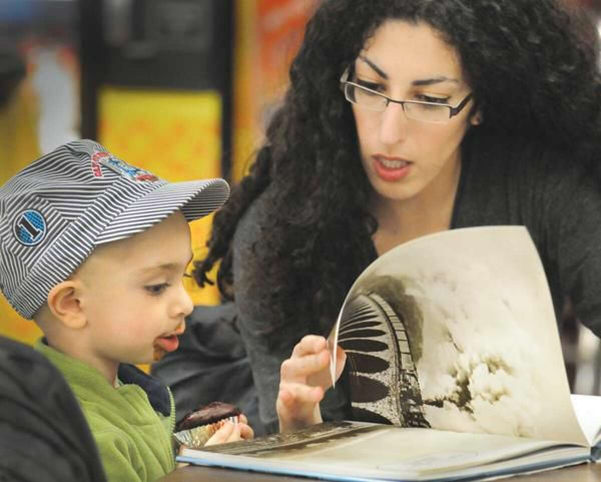 Photos by Melanie Stengel Yoavi Schmidt, 2, of Hamden, enjoys a cupcake as he and his mother, Adi, look over a book about trains.