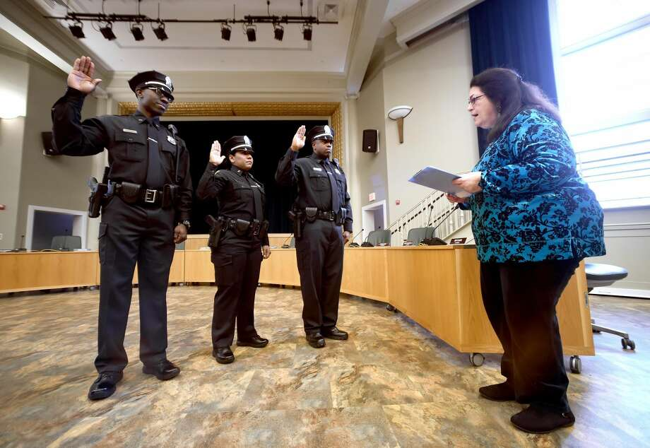 From left, Hamden Police Officers Keron Bryce, Jinett Marte and Michael White are sworn in by Town Clerk Vera Morrison at Hamden Memorial Town Hall.