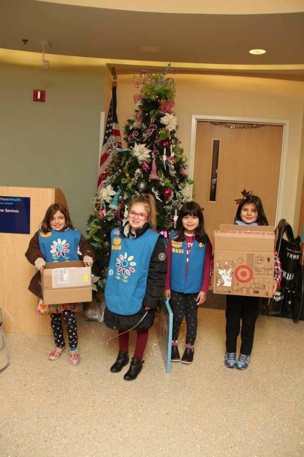 Girl Scouts Evelyn, Daniella, Avery, and Lily with some of the donated toys.