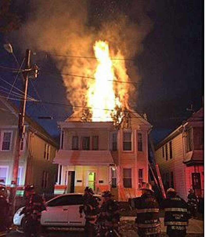 Flames shoot out from the third-floor of a house at 132-134 Shepard St. in Hamden on Thursday. Fire officials said a firefighter was injured fighting the Thanksgiving Day blaze and the building was declared uninhabitable.
