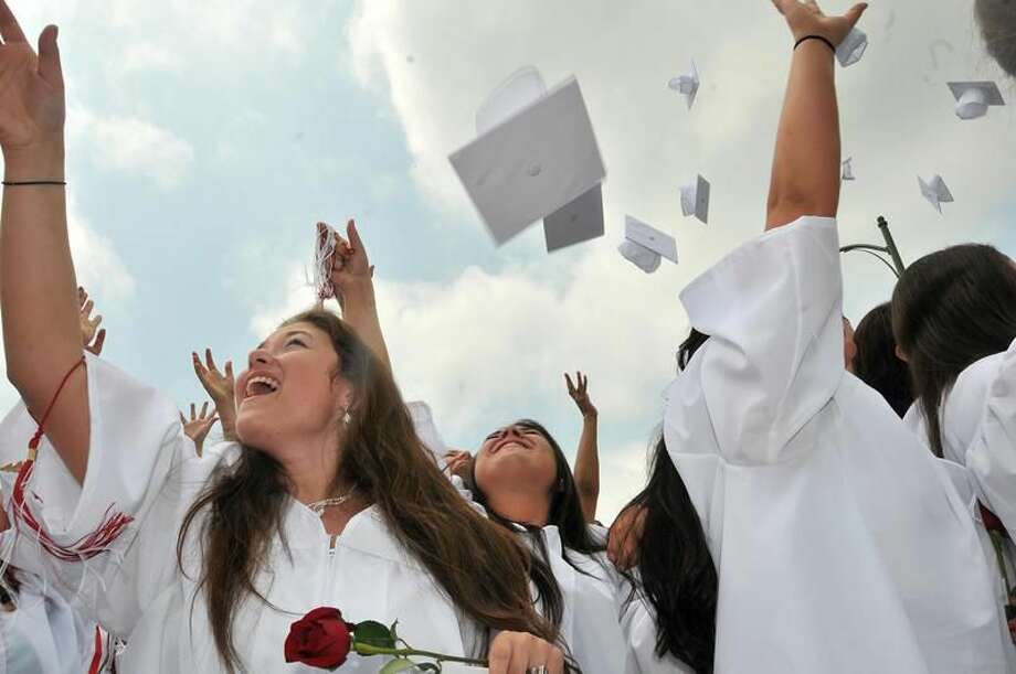 Photo by Brad Horrigan Sacred Heart Academy seniors toss their mortarboards into the air after commencement exercises Saturday in Hamden.