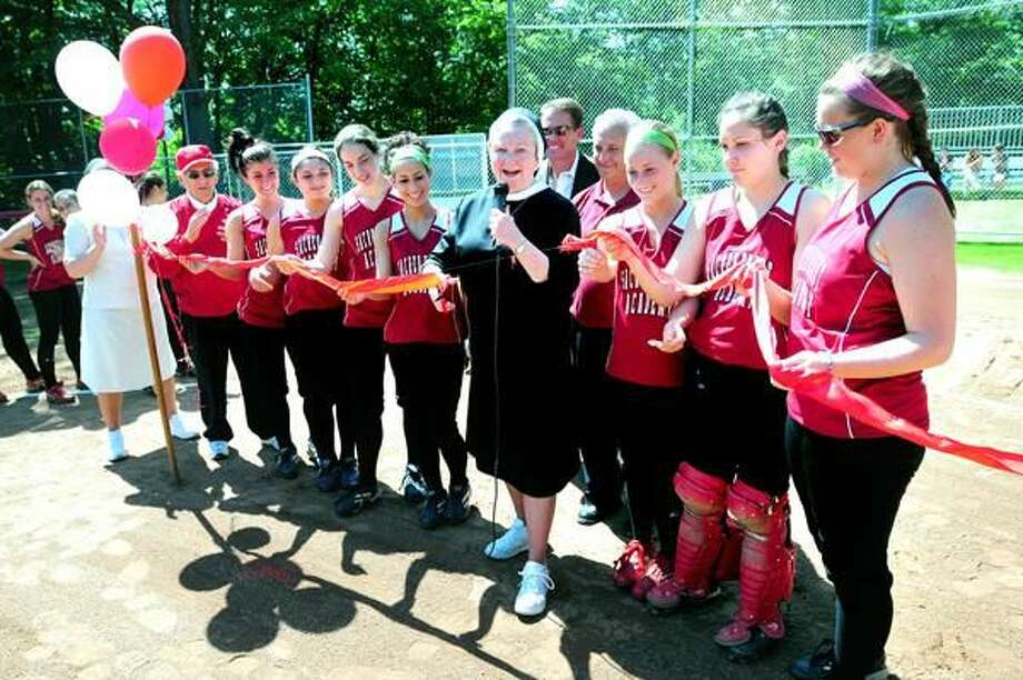Photo by Arnold Gold Sacred Heart Academy senior softball players surround Sister Sheila O'Neill (center), president of Sacred Heart Academy, during a ribbon cutting and rededication of the renovated E. William Iovanne Softball Field in Hamden before a game against North Haven Wednesday. William Iovanne is at left next to balloons.