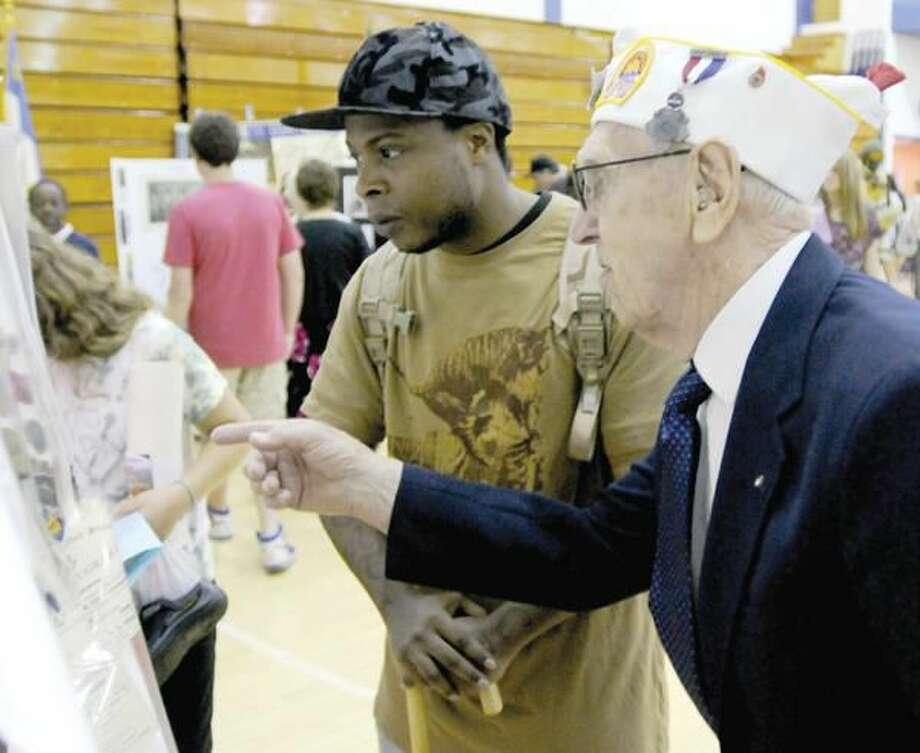 Photo by Peter Hvizdak U.S. Army Veterans Donald Erickson, 85, right, and Aaron Hawkins, left, look at military memorabilia Friday at the 11th annual Hamden Veterans Awareness Day held at Quinnipiac University.