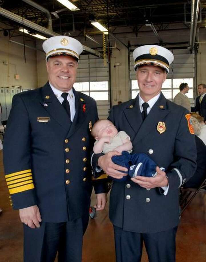 Photo by Caroline Kowalczyk David J. Macarelli holds his 10-week-old son, Grayson, at the North Haven Fire Commission meeting, where he became the new deputy fire chief. At left is Fire Chief Vincent Landisio.