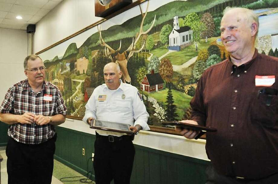 Photo by Melanie Stengel Master of Ceremonies Karl Olsen (L) and President, Peter Memmone (C) look on as Gil Spencer smiles holding a small replica of a larger plaque presented to him at the Mt. Carmel Volunteer Fire Station Company. The Company is celebrating it's 100 year reunion.