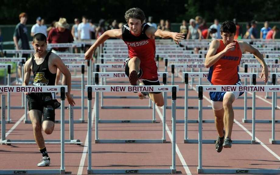 Photo by Mara Lavitt/Register Cheshire's Eric Zdanowski center won the hurdles, Amity's Jesse Sanchez, left, came in third at Class LL track championships.