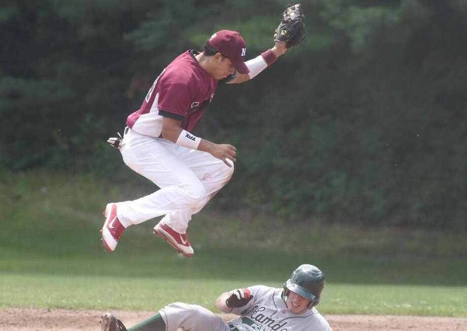Photo by Russ McCreven North Haven shortstop Edison Rodriguez leaps to catch the ball while a Hamden runner slides under him in a recent game.