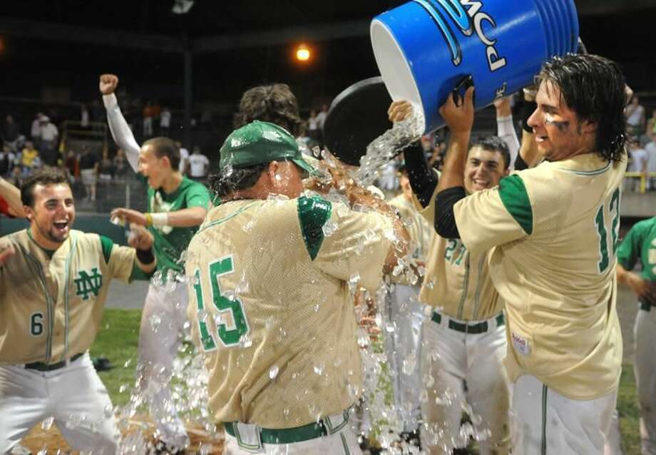 Photo by Melanie Stengel/Register Notre Dame pitcher Gary Flowers dumps water on coach Lou Kessler as they celebrate the championship. Jacob DeRosa in back.