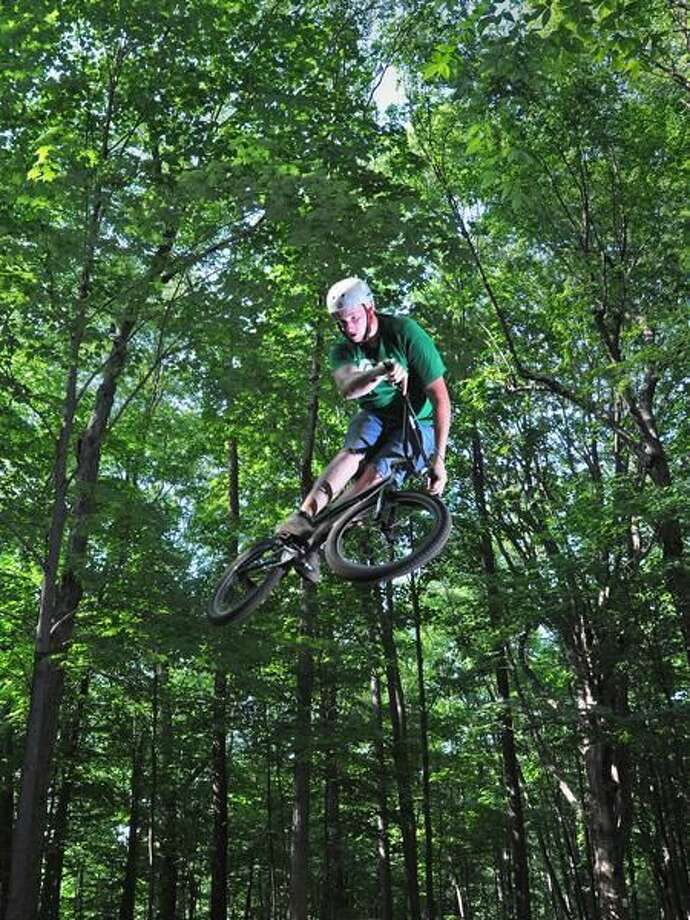 Dylan Shaw of Southington jumps from a ramp at Bassett Trails in Hamden Wednesday. The town Thursday began demolishing the ramps and trails Thursday, citing liability issues because the unsanctioned bike trails are on town land. Brad Horrigan/Register