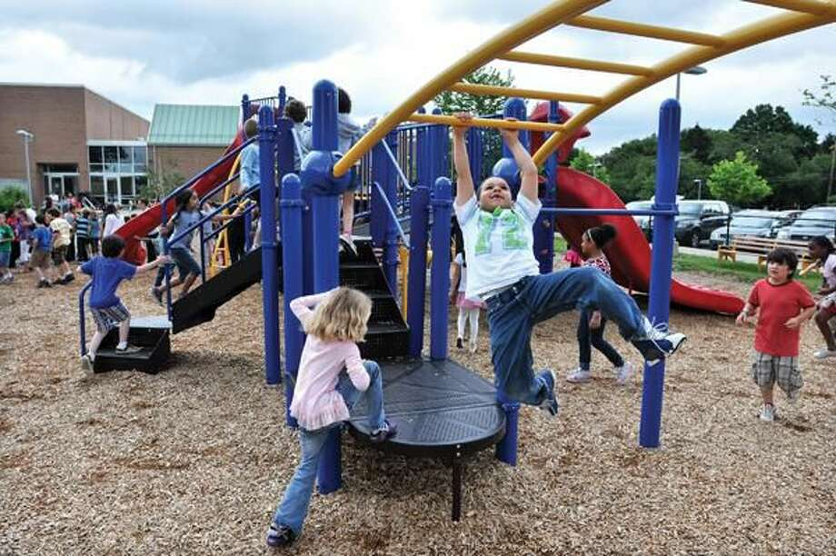 Photo by Peter Casolino 6-Year-old Ryan Borges plays on the new moments Spring Glen School Playground moments after the ribbon cutting ceremony.