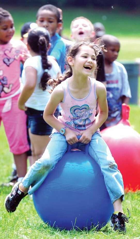 Photo by Arnold Gold Shepherd Glen School first-grader Aiyanna Colon, 6, takes her turn in the Bouncy Ball Relay during the annual field day at the school in Hamden Wednesday.
