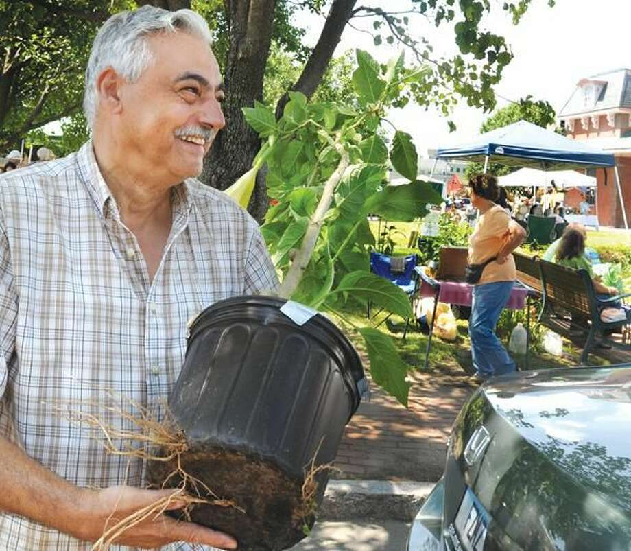 Richard Serio, of Wallingford, carries an Angel Trumpet to the car for a customer at the Wallingford Gardener's Market.