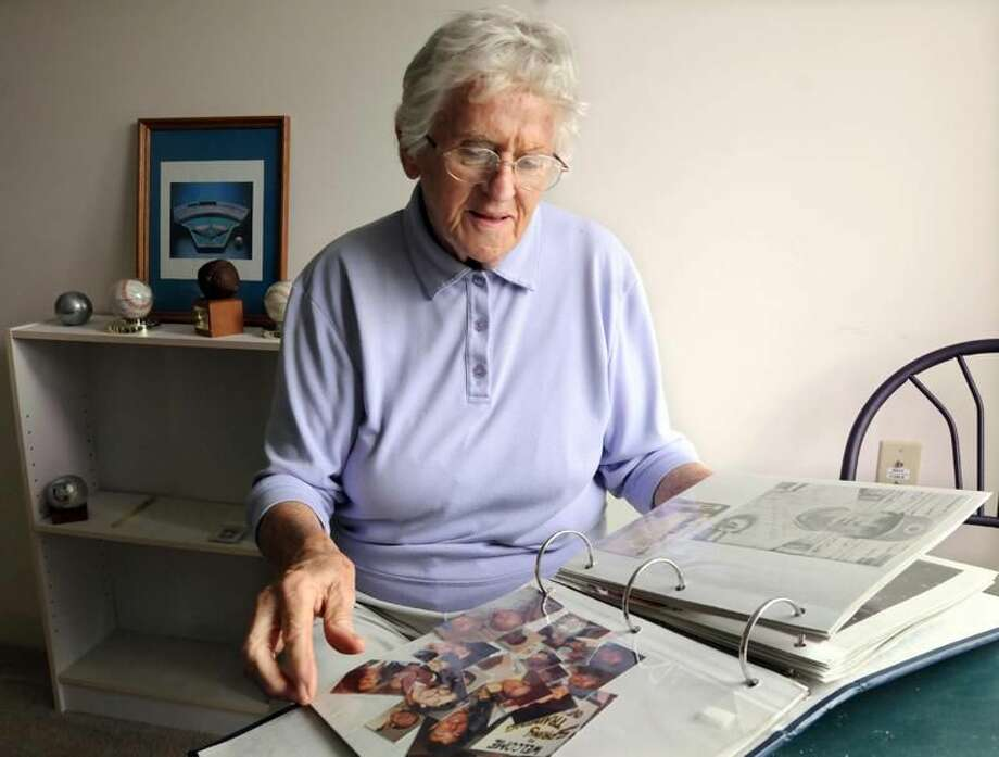 Photo by Mara Lavitt/Register Jean Kaas looks through a scrapbook of the baseball minor league players who she hosted while living in West Haven.