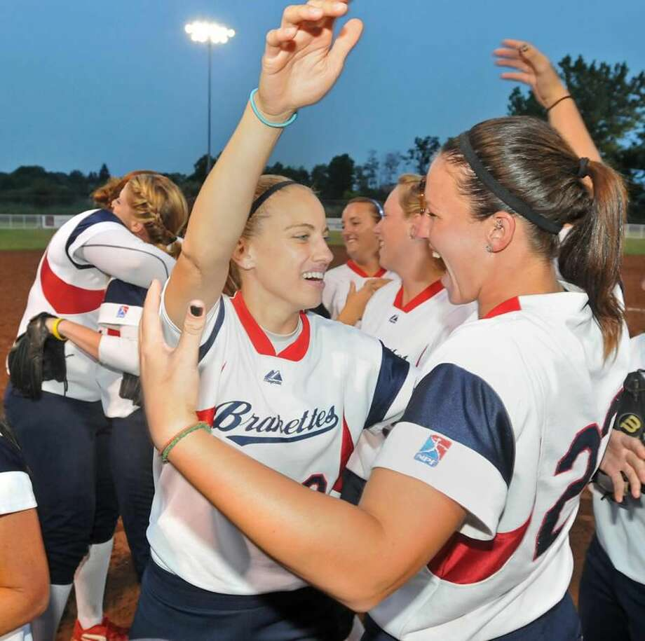 Photo by Brad Horrigan/Register Brakette shortstop Mandie Fishback, left, hugs first baseman Stephanie Call after the Connecticut Brakettes won the Women's Major Fast Pitch National Championship Sunday night at DeLuca Field in Stratford.