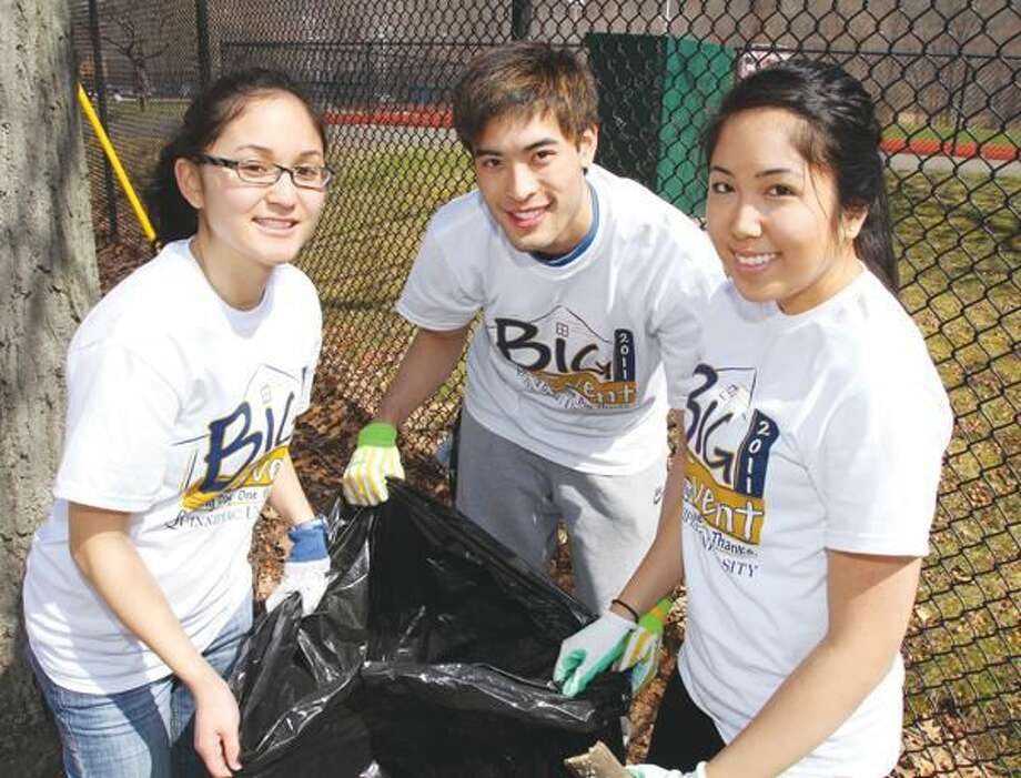 """Submitted Photo Quinnipiac University students Jessica Hoang, left, Nick Chin and Patricia Libid clean-up at East Rock Park in New Haven during """"The Big Event"""" community service day on April 9. More than 1,000 members of the Quinnipiac community spent the day volunteering in Greater New Haven as part of """"The Big Event."""""""