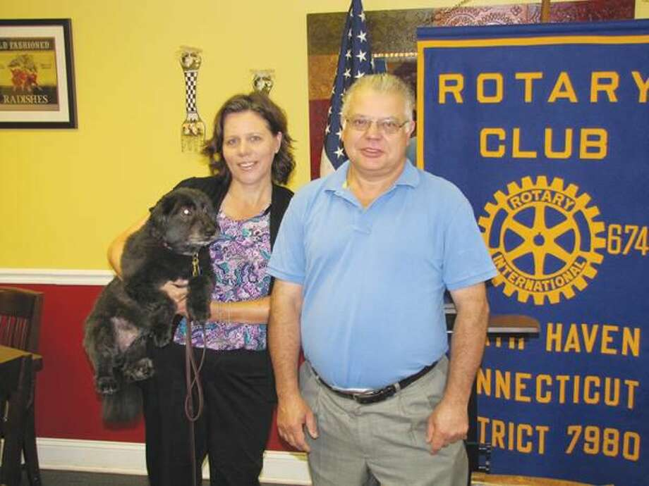 Kate Nicoll, left, of Soul Friends posed holding her guide dog prior to accepting a $500 check from Rotarian Luigi Nuzzolillo.