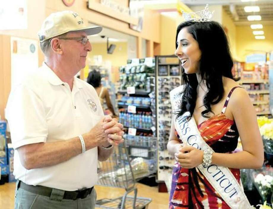 Photo by Peter Hvizdak Alton Hudson of North Haven, 70, a 23-year veteran of the U.S. Air Force, left, and Miss Connecticut, Morgan Amarone of North Haven, chat during a fundraising effort at Shop Rite in Hamden Saturday for Fisher House of Connecticut. The housing will be built at the VA hospital in West Haven for veterans families.