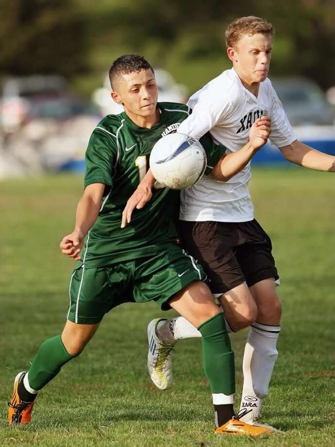 Photo by Todd Kalif/Middletown Press Hamden's Alex Zapata battles Xavier's Spencer Fletcher in Wednesday's game in Middltown. Zapata scored two goals to lead Hamden to a 2-1 victory.