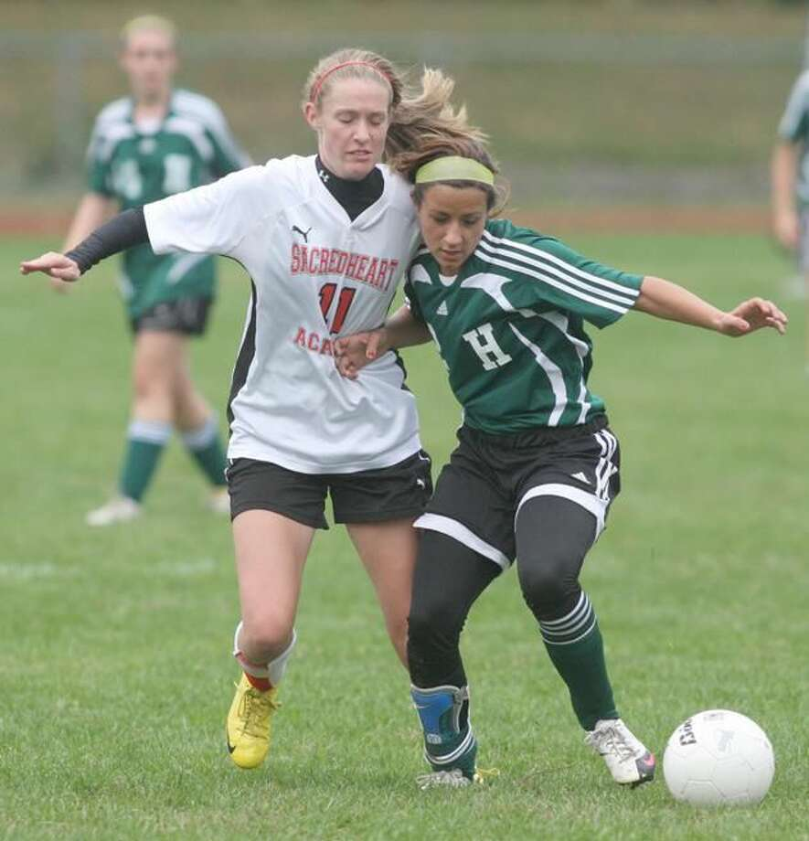File photo by Russ McCreven Sacred Heart's Libby Carlson (11) battles Hamden's Allegra Nottoli for the ball in a game played last season.