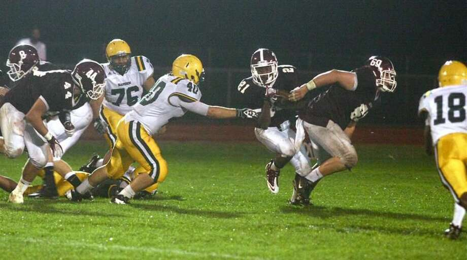 Photo by Russ McCreven Jalon White tries to run past Hamden's Tyler Stevens (40) while North Haven's Mark Zurlis (44) and Andrew Savenelli (60) prepare to block in the Indians' 28-25 win last Friday.
