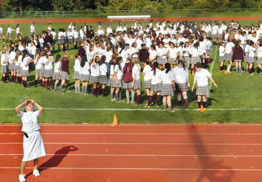 Photo by Melanie Stengel Sister Mary Jane Paolella looks for guidance from above as she tries to help Sacred Heart students get in formation for the school's 65th anniversary photograph. A photographer in an overhead bucket directed the shot.