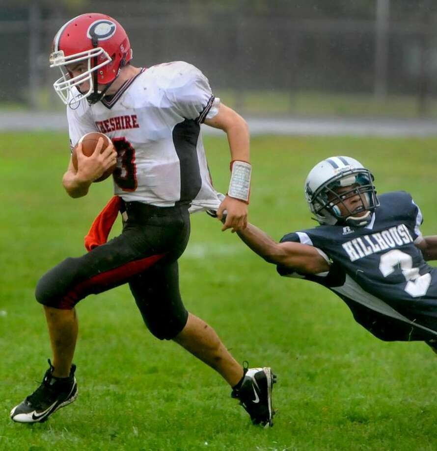 Photo by Peter Hvizdak/Register Cheshire's Michael John Ecke runs past Hillhouse defender Mike Washington during the second quarter of the Rams 30-6 victory Friday afternoon at Bowen Field in New Haven.