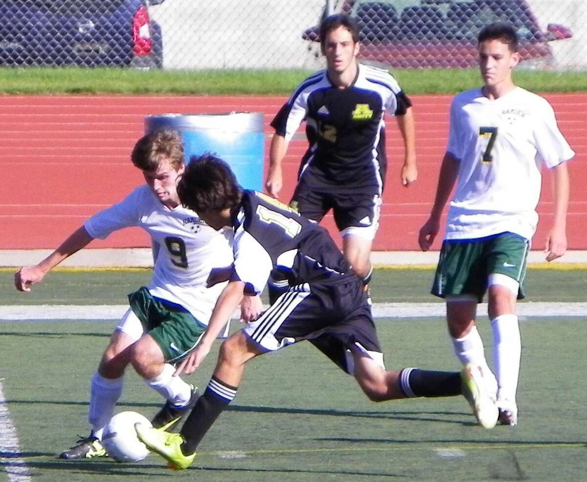 Submitted photo Hamden co-captain Jon Miller (left) battles an Amity player for the ball while Austin Tomin (7) looks on. Tomin scored the game-winning goal in the Dragons' 2-1 victory over the Spartans last Friday.