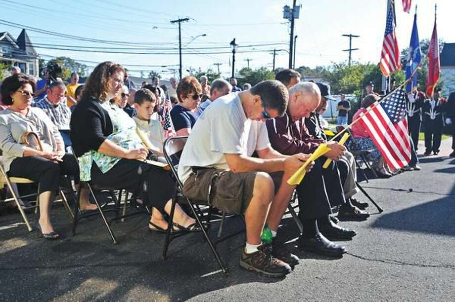 Photo by Peter Casolino People bow their heads in prayer, including Dana Andrews, front, during a 9/11 remembrance ceremony at the North Haven Fire headquarters. During the ceremony, the department honored 20 North Haven firefighters that responded to ground zero to help out in the recovery effort on 9/11 and the days that followed. Andrews is from North Haven.