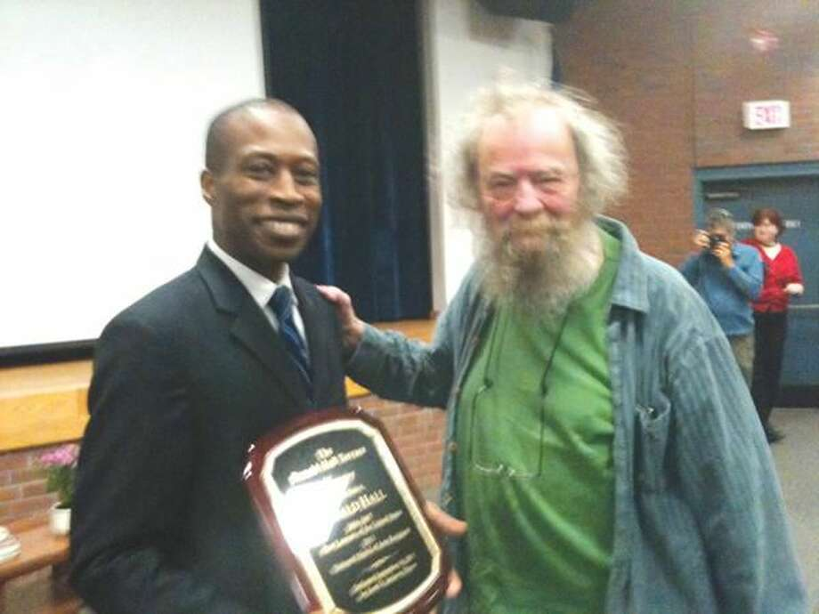 """Photo by Ann DeMatteo Hamden Mayor Scott Jackson presents a plaque to poet Donald Hall during the celebration at the Thornton Wilder Hall Friday night announcing that the gathering space outside the library would now be called the """"Donald Hall Terrace."""""""