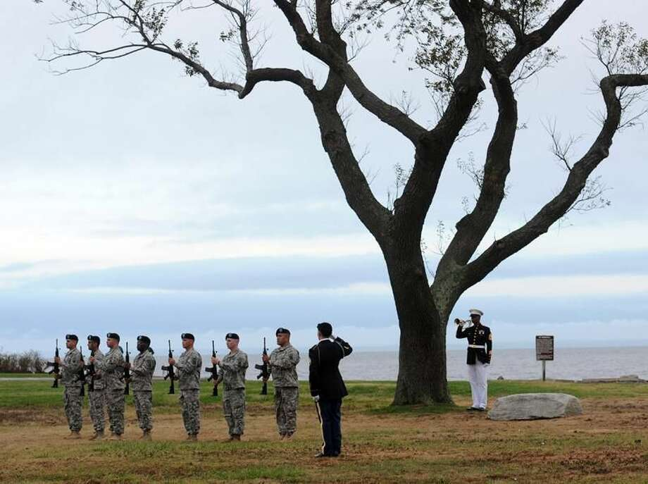 Photo by Peter Casolino A lone Marine bugler plays taps as an honor guard stands at attention during a memorial service Thursday at Sherwood Island State Park, home of the 9/11 Living Memorial.