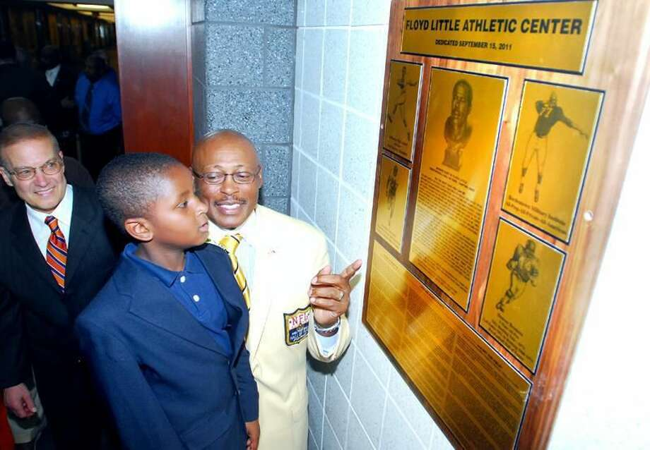 Photo by Arnold Gold/Register Bill Santillo, left, chairman of the dedication committee, watches football legend Floyd Little, right, show his grandson, Blaze Kennedy Jones, 6, the plaques honoring Little during the renaming of the New Haven Athletic Center the Floyd Little Athletic Center Thursday in New Haven.