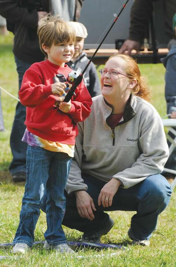 Photo by Mara Lavitt Mary Cozza, 6, of Hamden practices casting with a fishing rod at The Brooksvale Park Fall Festival in Hamden while mom Shannon gives pointers.