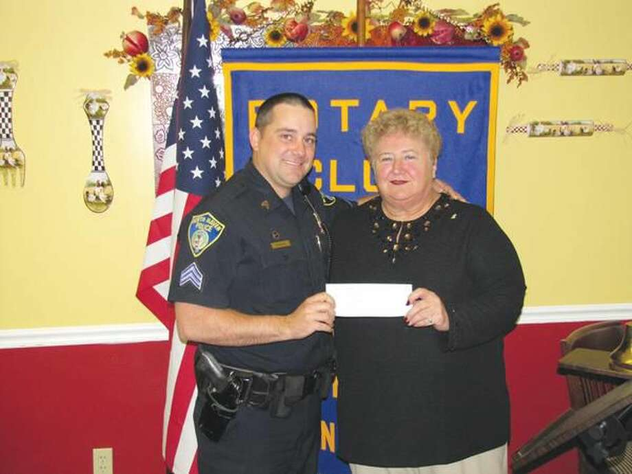 Submitted photo courtesy of David Marchesseault, Rotary PR Chairman North Haven Police Sergeant Christopher Thorpe accepts the annual contribution for D.A.R.E. from Rotarian Mary Jane Mulligan.