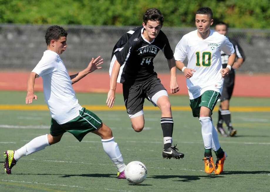 Photo by Mara Lavitt/Register Hamden's Luis Sandoval, left, and Alex Zapata, right, try to slow down Xavier's Callan Noone.
