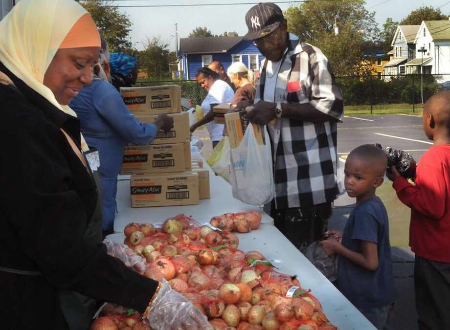 Photo by Melanie Stengel Volunteer Khadijah Mohammed, left, helps distribute food from the Connecticut Food Bank Truck Friday. Collecting groceries are, from left, Curtis Douglas, Jaihaziel Garrett, 5, and Kahanyjal Garrett, 9. The truck brought food to the Abdul-Majid Karim Hasan Islamic Center in Hamden.