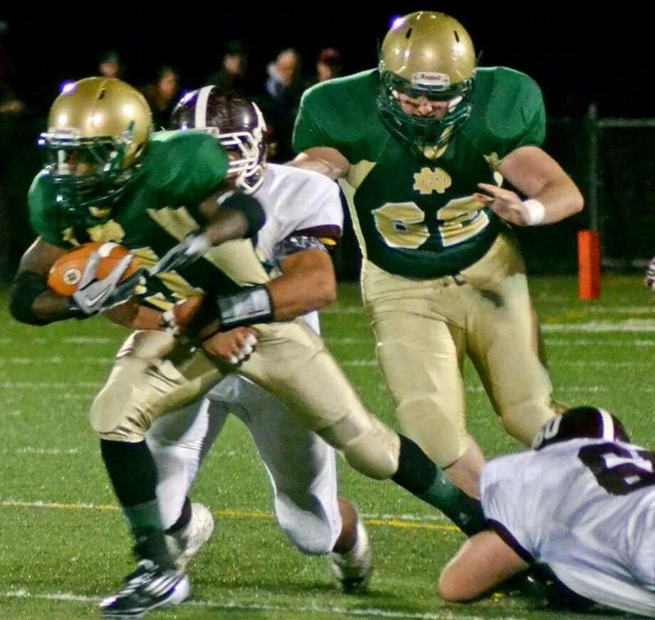 Photo by Sean Meenaghan/Register Notre Dame-West Haven running back Shawndel Evans fights for extra yards while North Haven's Andrew Savenelli tries to take him down in the Green Knights' 27-12 victory Friday night.