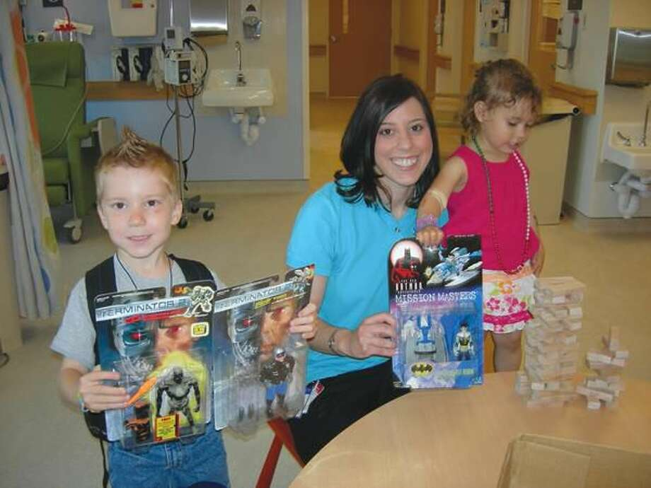 Submitted Photo Pictured is Erica Schwartz, a Child Life Specialist-Pediatric Specialty at Yale New Haven Children's Cancer Center, accepting donations from Gabriel and Hailey Ciarleglio.