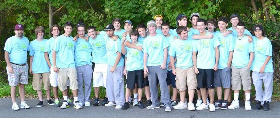 Submitted photo The North Haven hockey team accompanied by new head coach Tom Roche.
